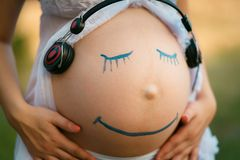 Pregnant woman belly closeup with smiling funny face drawing on. It, listening to the music in earphones stock image