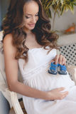 Pregnant woman belly holding baby booties. Stock Photos