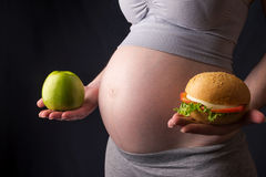 Pregnant woman belly holding a plate with junk and healthy food. Concept choice of diet during pregnancy. A pregnant woman belly holding a plate with junk and stock images