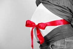 Pregnant woman belly with ribbon Royalty Free Stock Images