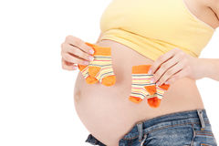 Pregnant woman belly and twin socks. Picture of beautiful pregnant woman belly and twin socks stock photo