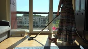 Pregnant woman with big belly in dress with vacuum cleaner hoover room stock video footage