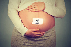 Pregnant woman big belly with sand clock sign Royalty Free Stock Images