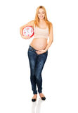 Pregnant woman with a big clock Stock Images