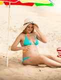 Pregnant woman in bikini applying suntan creme Stock Photos