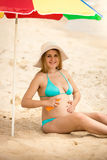 Pregnant woman in bikini sitting under parasol and applying sunb Stock Images