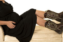 Pregnant woman in black dress and boots body sitting Stock Photo