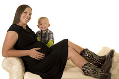 Pregnant woman in black dress and boots sitting by young boy Stock Photos