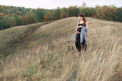 Pregnant woman in black dress and dreadlocks on the background of wild nature royalty free stock photo