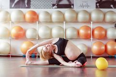 Healthy pregnant woman doing gymnastic royalty free stock photos