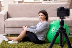 The pregnant woman blogger doing physical exercises royalty free stock image