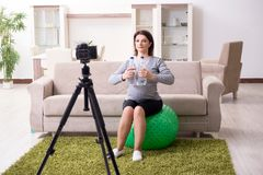 The pregnant woman blogger doing physical exercises stock photography