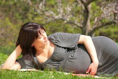Pregnant woman in blossom garden Royalty Free Stock Image