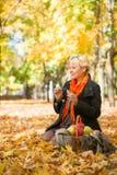 Pregnant woman blow bubbles in autumn park Stock Photos