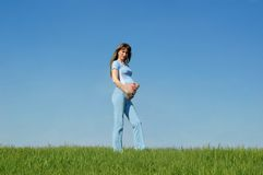 Pregnant woman on blue. Sky background Royalty Free Stock Photography