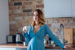 Pregnant woman in blue clothes with cup of tea or coffee. Young redhead pregnant woman in blue clothes with cup of tea or coffee at home in morning time Royalty Free Stock Image