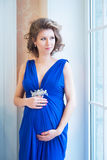 Pregnant woman in blue dress near window Royalty Free Stock Photos
