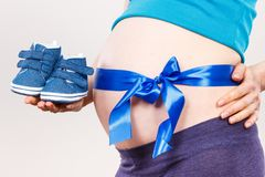Pregnant woman with blue ribbon on belly holding baby shoes, expecting for newborn concept royalty free stock image