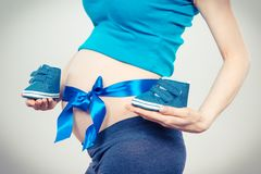 Pregnant woman with blue ribbon on belly holding baby shoes, concept of expecting for newborn. Pregnant woman with blue ribbon on belly holding baby shoes stock image