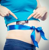 Pregnant woman with blue ribbon and ultrasound scan of baby on belly, concept of expecting for boy. Pregnant woman with blue ribbon and ultrasound scan of baby royalty free stock photos