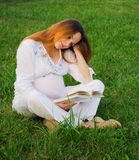 Pregnant woman with book stock photo