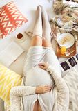 Pregnant woman with book, tea, cake relaxing at home Stock Photography