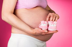 Pregnant woman with booties for future girls on  pink background. Royalty Free Stock Photo