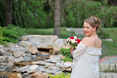Pregnant woman with bouquet. Pregnant woman outdoors in a park holding bouquet Royalty Free Stock Photo