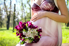 Pregnant woman with a bouquet of flowers in a summer park Royalty Free Stock Photo