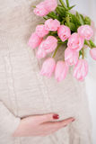Pregnant woman with bouquet of tulips touch bell. close up stock photo