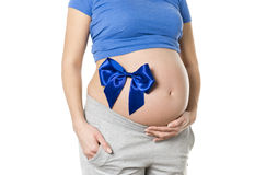 Pregnant woman with bow on belly. Pregnant woman with bow on belly - shoot showing a gift concept Stock Image