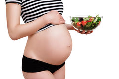 Pregnant woman with a bowl of vegetables. Healthy nutrition and pregnancy. Close-up pregnant woman's belly and vegetable salad Royalty Free Stock Images