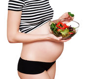 Pregnant woman with a bowl of vegetables. Healthy nutrition and pregnancy. Close-up pregnant woman's belly and vegetable salad Stock Photography