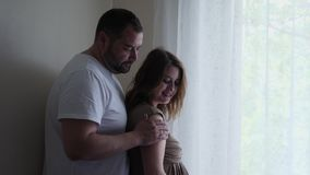 Pregnant woman in a brown dress and her husband in a white t-shirt stock video