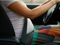 A pregnant woman buttoned up safety belt Stock Images