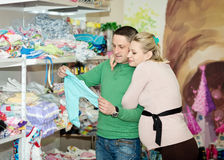 Pregnant woman buying baby clothes in supermarket. Pregnant women buying baby clothes in supermarket . Young pregnant women choosing newborn clothes royalty free stock photos