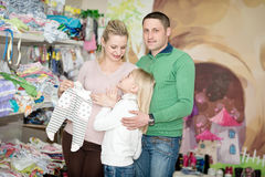 Pregnant woman buying baby clothes in supermarket. Pregnant women buying baby clothes in supermarket . Young pregnant women choosing newborn clothes stock photo