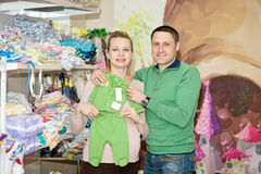 Pregnant woman buying baby clothes in supermarket. Pregnant women buying baby clothes in supermarket . Young pregnant women choosing newborn clothes royalty free stock photo