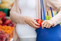 Pregnant woman buying food at street market Royalty Free Stock Photos