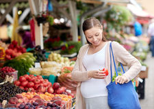 Pregnant woman buying food at street market Stock Photos