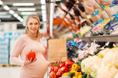 Pregnant woman buying vegetables at grocery store stock photos