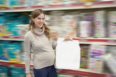 Pregnant woman buys diapers at the supermarket Royalty Free Stock Photos