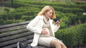Pregnant woman calling hospital phone, suffering abdominal pain, prenatal care. Stock photo royalty free stock photo