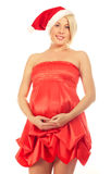 Pregnant woman caressing her belly wearing Santa Hat Royalty Free Stock Image