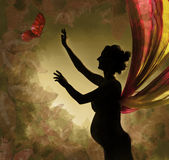 Pregnant woman catching butterfly. Pregnant woman with wings catching buterfly. Naked silhouette.  Vintage background with butterflies Stock Photo