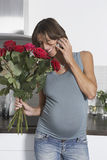 Pregnant Woman With Cellphone And Roses Stock Photos