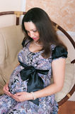 The pregnant woman in a chair Royalty Free Stock Images