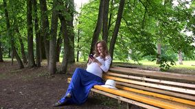 Pregnant woman chatting on cell phone while sitting on park bench outdoors. Female experience positive emotions. Pregnancy in nature. Handheld steadycam flycam stock video