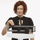 Pregnant woman checking her weight. Royalty Free Stock Photography