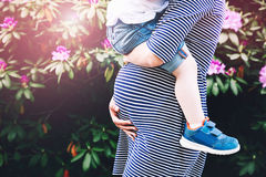 Pregnant woman with child on nature background, close-up. Pregnant women with child. Mother and son on nature background, close-up. Child boy is sitting on Royalty Free Stock Image
